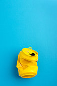 Used and crumpled yellow aluminium soda can on blue background.