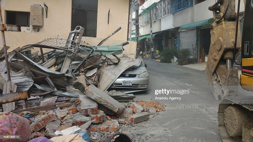 Crushed car beneath a residential building in Rende District, Tainan is seen on February 6, 2016 following a strong earthquake struck Taiwan. At least 13 people including a baby girl were confirmed dead Saturday after a magnitude 6.4 earthquake hit southern Taiwan, collapsing buildings and injuring hundreds of others.