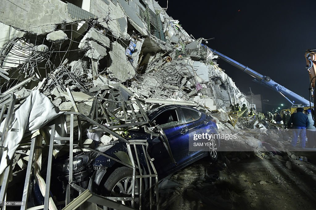A crushed car is seen at the site of a collapsed building in the southern Taiwanese city of Tainan on February 6, 2016 following a strong 6.4-magnitude earthquake. A powerful earthquake in Taiwan felled a 16-storey apartment complex full of families who had gathered for Lunar New Year celebrations in the early hours of February 6, with at least seven dead and more than 30 feared trapped. AFP PHOTO / Sam Yeh / AFP / SAM YEH