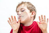 crushed young boy touching his goofy face and cheek to a window with his hands for concept of fear with humor, white background