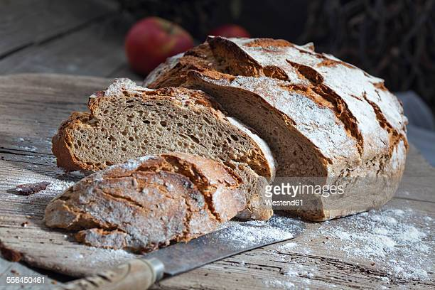 Crusty bread and old bread knife on chopping board