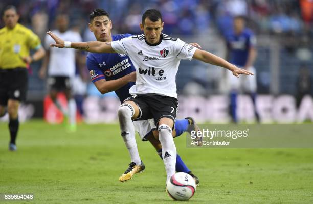 Cruz Azul's midfielder Felipe Mora vies for the ball with Atlas midfielder Daniel Arreola during their Mexican Apertura tournament football match at...