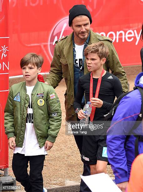 Cruz Beckham and David Beckham congratulate Romeo Beckham after he completed the Junior Marathon during the London Marathon on April 26 2015 in...