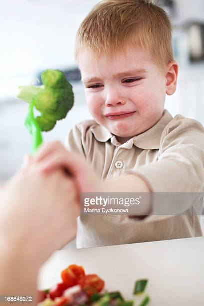 Crying boy refusing broccoli in kitchen