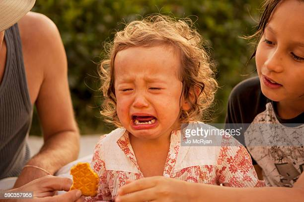 Crying child at picnic table, others comforting