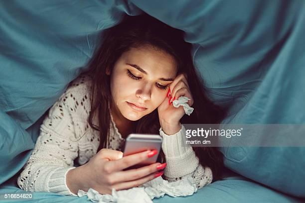 Jeune fille en pleurs lit envoyer des SMS sur un smartphone