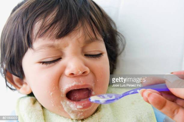 Crying Hispanic baby being fed