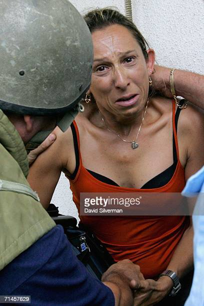 A crying Israeli television camerawoman is comforted at the scene where a Hezbollah missile struck a railways depot as sirens wail to announce...