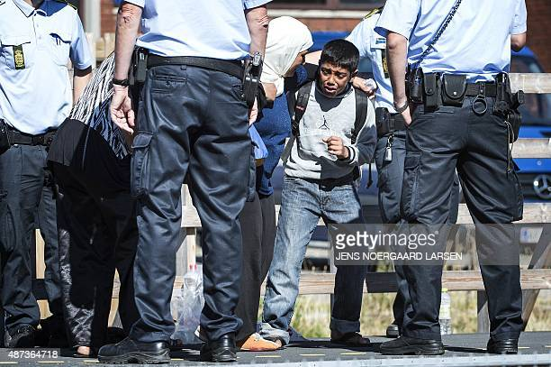 A crying migrant child tries to prevent his mother from leaving a train to get into a bus at Rodby railway station southern Denmark on September 9...