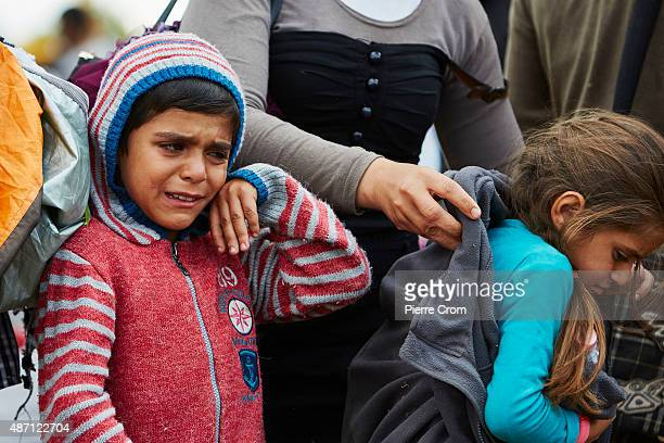 A crying migrant child wipes their face as Hungarian police assemble migrants who have crosssed the border from Serbia as they journey into Europe on...