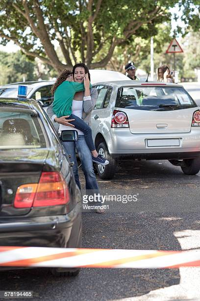 Crying mother witg daughter at car accident scene on the phone