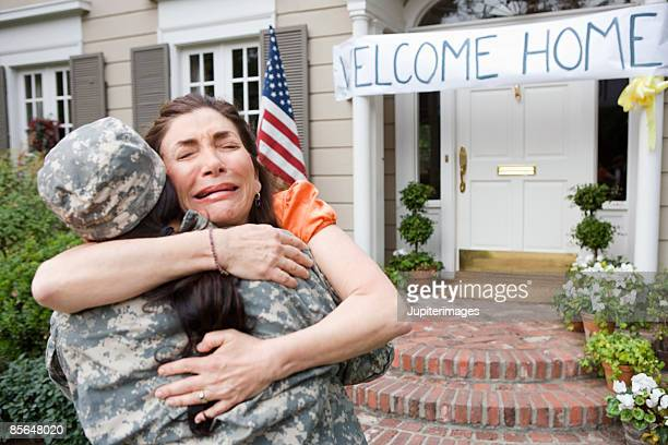 Crying woman embracing soldier