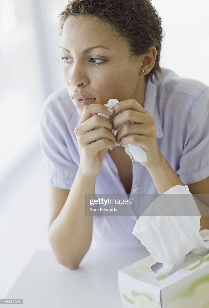 Crying woman holding tissue : Stock Photo