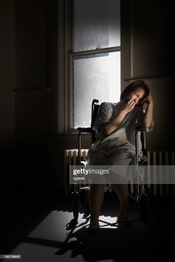 Crying Woman Sitting in Wheelchair by Window, Low Key : Stock Photo