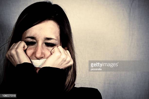 Crying Woman with Tape Covering Mouth