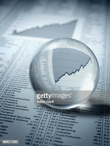 Crystal ball, ascending line graph and share prices : Foto de stock