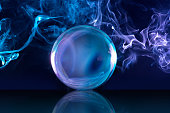 crystal ball and bluish smoke in dark background