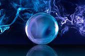 crystal ball and bluish smoke in dark background