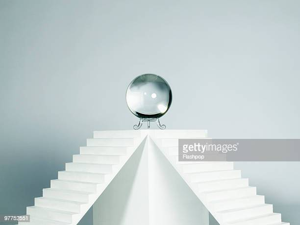 Crystal ball sitting on top of plinth