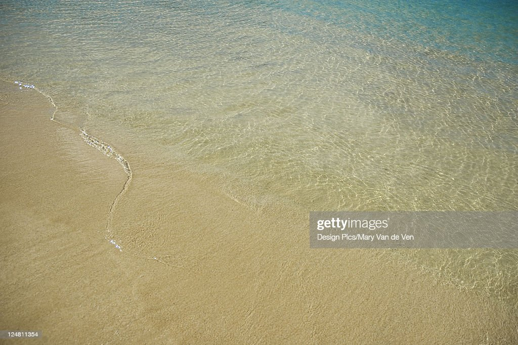 crystal clear shallow ocean water washes over sandy beach