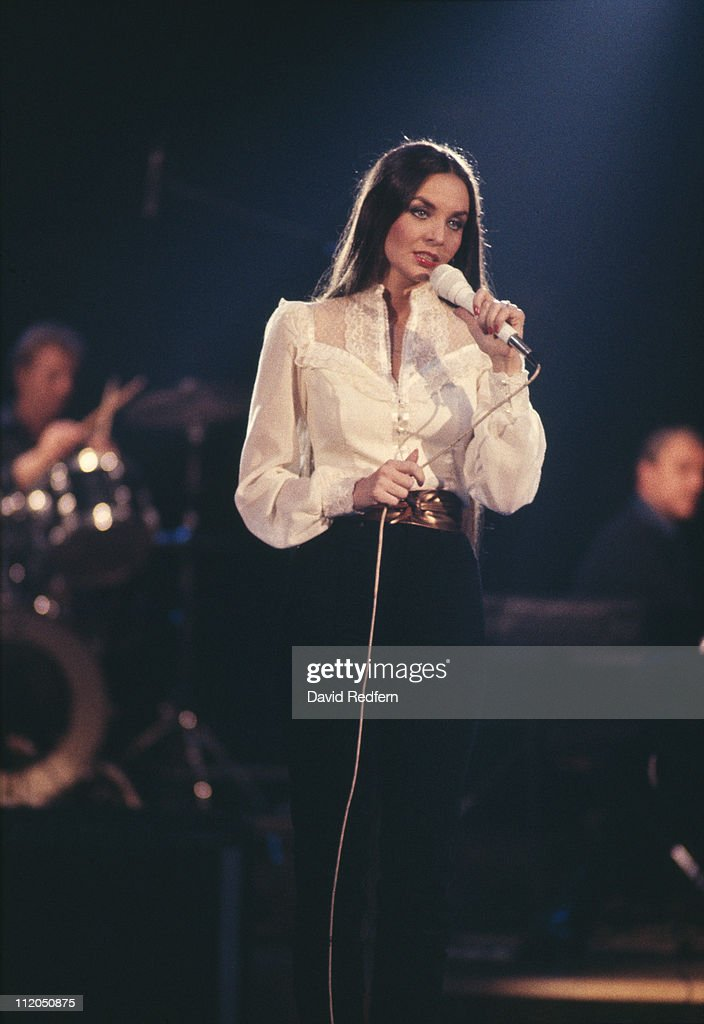 <a gi-track='captionPersonalityLinkClicked' href=/galleries/search?phrase=Crystal+Gayle&family=editorial&specificpeople=1537366 ng-click='$event.stopPropagation()'>Crystal Gayle</a>, U.S. country music singer, singing into a microphone during a concert, circa 1975.