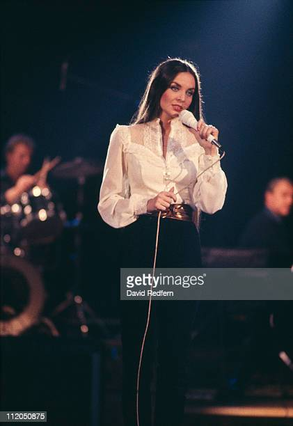 Crystal Gayle US country music singer singing into a microphone during a concert circa 1975