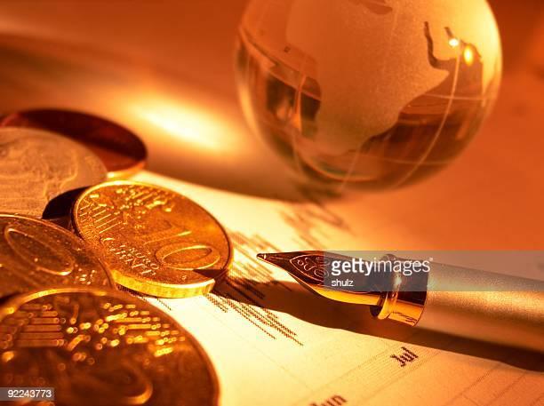 Crystal mondo, monete e penna stilografica su stock pagina