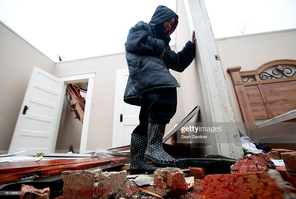Crystal Hamilton walks through her living room a day after a tornado touched down on February 11, 2013 in Hattiesburg, Mississippi. Hundreds of homes were destroyed and over sixty people injured when the tornado ripped through the town.