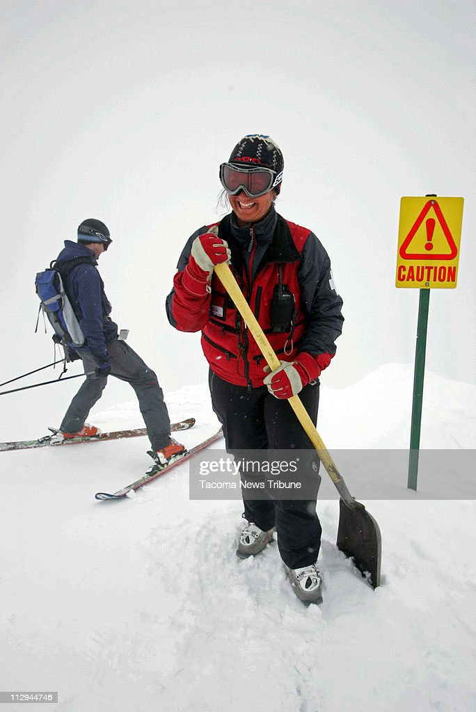 Crystal Mountain ski patrol member Lisa Poncelet warns skiers that there is no easy way down as they descend toward powder bowl from the High Campbell chair that serves purely double black diamond runs, Saturday, March 31, 2007.