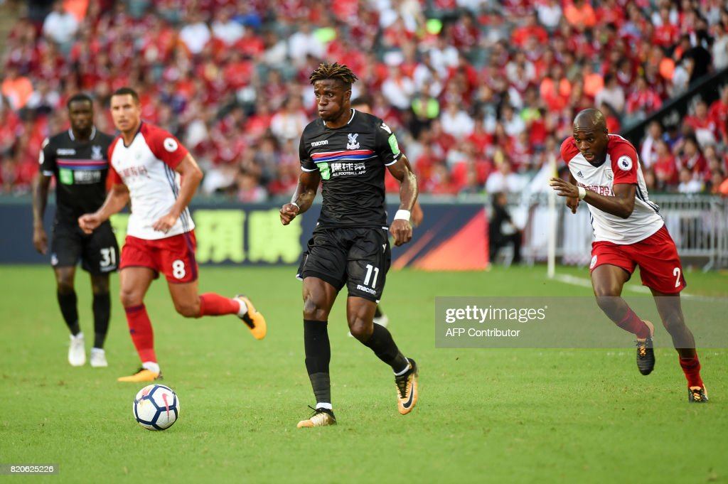 Crystal Palace midfielder Wilfried Zaha (C) controls the ball during the third-place playoff match of the Premier League Asia Trophy football tournament between West Bromwich Albion and Crystal Palace in Hong Kong on July 22, 2017. / AFP PHOTO / Isaac LAWRENCE / RESTRICTED TO EDITORIAL USE. No use with unauthorized audio, video, data, fixture lists, club/league logos or 'live' services. Online in-match use limited to 75 images, no video emulation. No use in betting, games or single club/league/player publications.