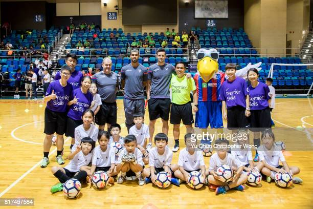 Crystal Palace players Ruben LoftusCheek Scott Dann Gary Mulcahey the football club's mascot pose for a photo with the young soccer fans during the...