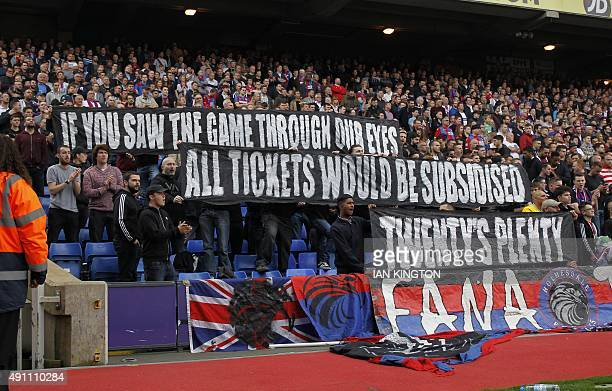 Crystal Palace supporters hold up banners about ticket prices at the start of the second half of the English Premier League football match between...