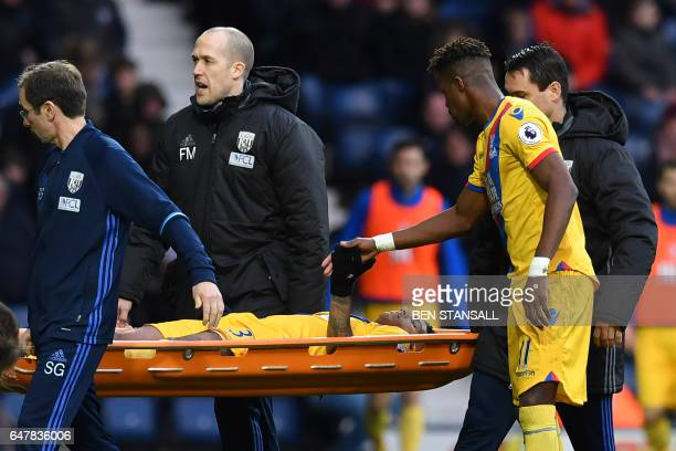 Crystal Palace's Dutch defender Patrick van Aanholt is taken from the field on a stretcher after picking up an injury during the English Premier...