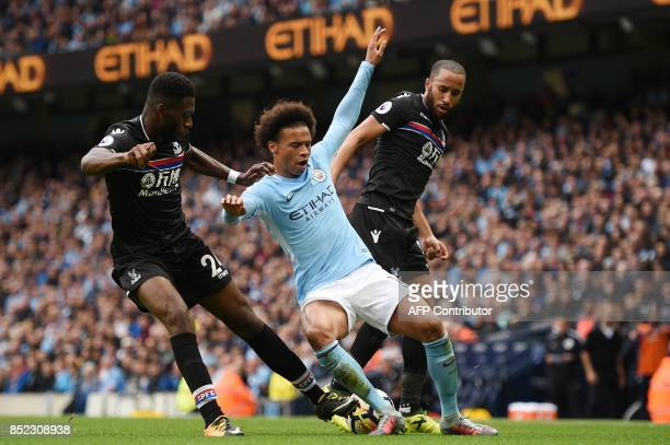 Crystal Palace's Dutch defender Timothy FosuMensah and Crystal Palace's English midfielder Andros Townsend tackled Manchester City's German...