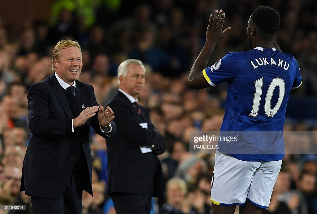 Crystal Palace's English manager Alan Pardew (C) reacts as Everton's Belgian striker Romelu Lukaku (R) celebrates scoring his team's first goal with Everton's Dutch manager Ronald Koeman during the English Premier League football match between Everton and Crystal Palace at Goodison Park in Liverpool, north west England on September 30, 2016. / AFP / PAUL ELLIS / RESTRICTED TO EDITORIAL USE. No use with unauthorized audio, video, data, fixture lists, club/league logos or 'live' services. Online in-match use limited to 75 images, no video emulation. No use in betting, games or single club/league/player publications. /