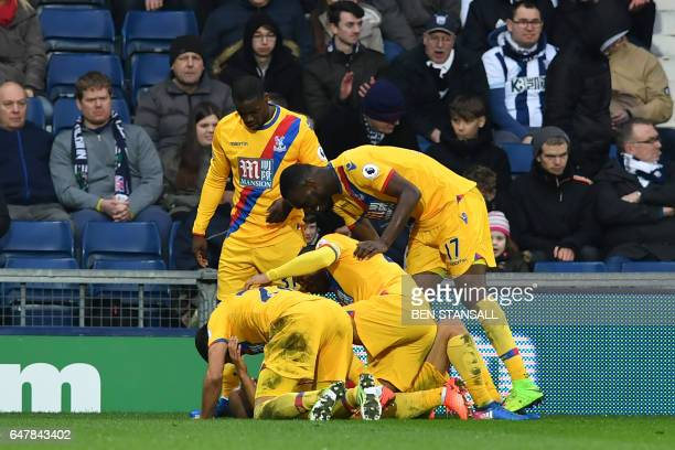 Crystal Palace's English midfielder Andros Townsend is congratulated by teammates after scoring their second goal during the English Premier League...