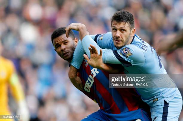 Crystal Palace's Frazier Campbell left and Manchester City's Martin Demichelis wrestle