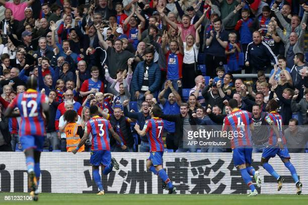 Crystal Palace's French midfielder Yohan Cabaye celebrates with teammates after scoring Crystal Palace's first league goal of the season during the...