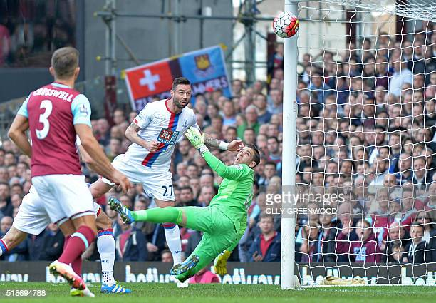 Crystal Palace's Irish defender Damien Delaney scores the opening goal past West Ham United's Spanish goalkeeper Adrian during the English Premier...