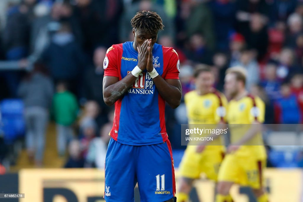 Crystal Palace's Ivorian striker Wilfried Zaha reacts after they concede their second goal during the English Premier League football match between Crystal Palace and Burnley at Selhurst Park in south London on April 29, 2017. Burnley won the game 2-0. / AFP PHOTO / Ian KINGTON / RESTRICTED TO EDITORIAL USE. No use with unauthorized audio, video, data, fixture lists, club/league logos or 'live' services. Online in-match use limited to 75 images, no video emulation. No use in betting, games or single club/league/player publications. /
