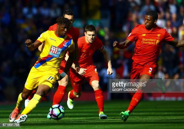 Crystal Palace's Ivorian striker Wilfried Zaha runs past Liverpool's English midfielder James Milner and Liverpool's Dutch midfielder Georginio...