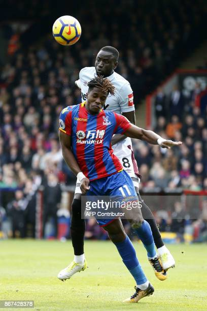 Crystal Palace's Ivorian striker Wilfried Zaha vies with West Ham United's Senegalese midfielder Cheikhou Kouyate during the English Premier League...