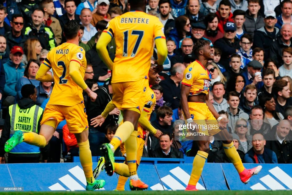 Crystal Palace's Ivorian-born English striker Wilfried Zaha (R) celebrates after scoring their first goal during the English Premier League football match between Chelsea and Crystal Palace at Stamford Bridge in London on April 1, 2017. / AFP PHOTO / Ian KINGTON / RESTRICTED TO EDITORIAL USE. No use with unauthorized audio, video, data, fixture lists, club/league logos or 'live' services. Online in-match use limited to 75 images, no video emulation. No use in betting, games or single club/league/player publications. /