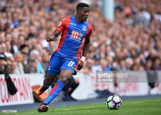 Crystal Palace's Ivorianborn English striker Wilfried Zaha runs with the ball during the English Premier League football match between Tottenham...