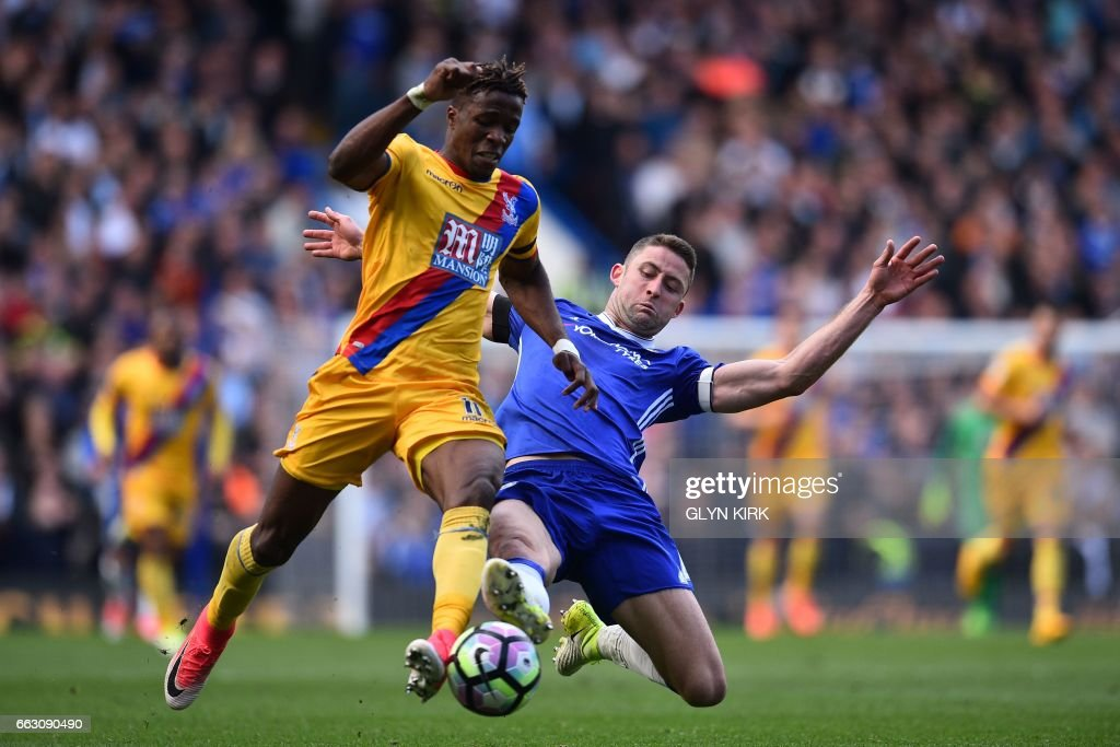 TOPSHOT - Crystal Palace's Ivorian-born English striker Wilfried Zaha (L) vies with Chelsea's English defender Gary Cahill during the English Premier League football match between Chelsea and Crystal Palace at Stamford Bridge in London on April 1, 2017. / AFP PHOTO / Glyn KIRK / RESTRICTED TO EDITORIAL USE. No use with unauthorized audio, video, data, fixture lists, club/league logos or 'live' services. Online in-match use limited to 75 images, no video emulation. No use in betting, games or single club/league/player publications. /