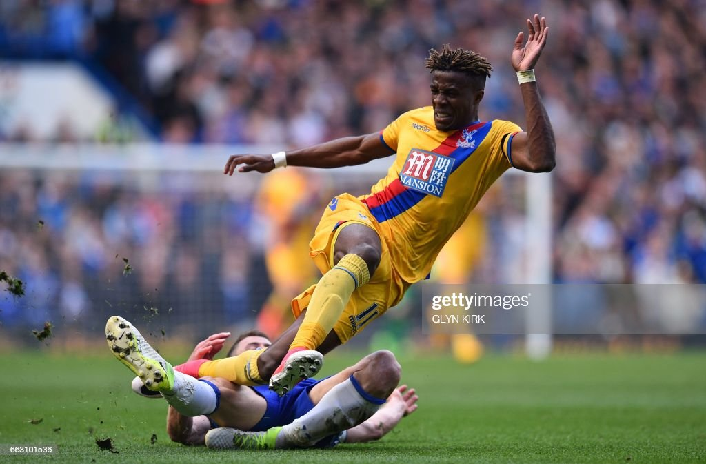 TOPSHOT - Crystal Palace's Ivorian-born English striker Wilfried Zaha (up) vies with Chelsea's English defender Gary Cahill during the English Premier League football match between Chelsea and Crystal Palace at Stamford Bridge in London on April 1, 2017. / AFP PHOTO / Glyn KIRK / RESTRICTED TO EDITORIAL USE. No use with unauthorized audio, video, data, fixture lists, club/league logos or 'live' services. Online in-match use limited to 75 images, no video emulation. No use in betting, games or single club/league/player publications. /