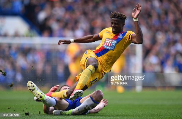 TOPSHOT Crystal Palace's Ivorianborn English striker Wilfried Zaha vies with Chelsea's English defender Gary Cahill during the English Premier League...