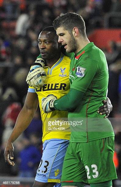 Crystal Palace's Nigerian striker Shola Ameobi is consoled by Southampton's English goalkeeper Fraser Forster at the final whistle in the English...