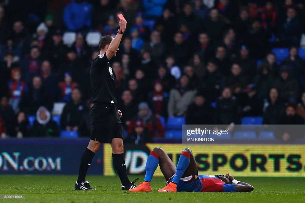 Crystal Palace's Senegalese defender Pape Souare (R) is shown a red card by referee Robert Madley (L) during the English Premier League football match between Crystal Palace and Watford at Selhurst Park in south London on February 13, 2016. / AFP / Ian Kington / RESTRICTED TO EDITORIAL USE. No use with unauthorized audio, video, data, fixture lists, club/league logos or 'live' services. Online in-match use limited to 75 images, no video emulation. No use in betting, games or single club/league/player publications. /