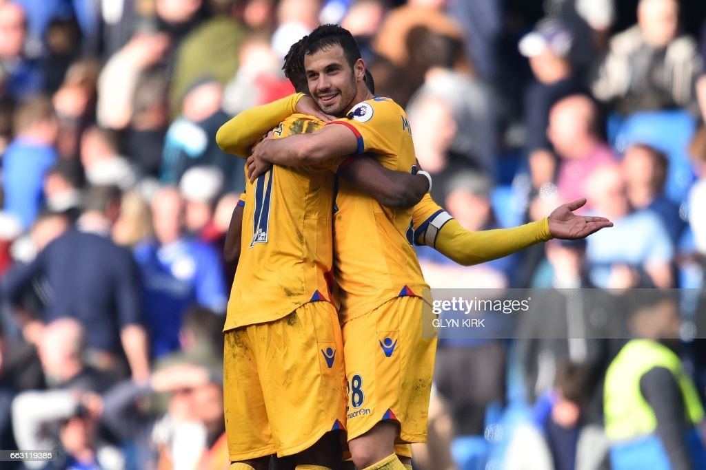 Crystal Palace's Serbian midfielder Luka Milivojevic (R) and Crystal Palace's Ivorian-born English striker Wilfried Zaha embrace on the pitch at the final whistle in the English Premier League football match between Chelsea and Crystal Palace at Stamford Bridge in London on April 1, 2017. Crystal Palace won the game 2-1. / AFP PHOTO / Glyn KIRK / RESTRICTED TO EDITORIAL USE. No use with unauthorized audio, video, data, fixture lists, club/league logos or 'live' services. Online in-match use limited to 75 images, no video emulation. No use in betting, games or single club/league/player publications. /